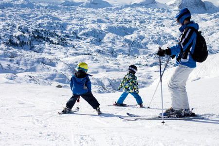 Father and two boys, skiing on a sunny day on a mountain summit in Austria resort, winter time