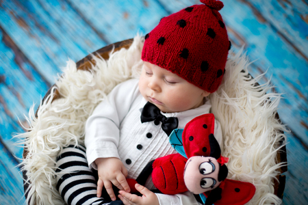 Little baby boy with knitted ladybug hat and pants in a basket, sleeping peacefully in a basket, isolated studio shot