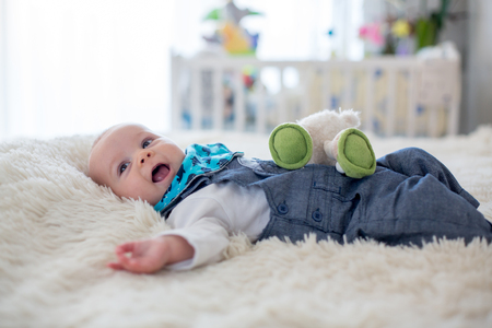 Little cute baby boy, playing with toys at home, smiling at camera, wintertime