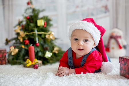 Portrait of newborn baby in Santa clothes and christmas hat, lying on the ground, winter snow landscape outdoor Stock Photo