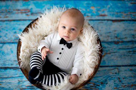 Little baby boy, dressed as a little gentlemen, with bow, smiling happily at camera Stock fotó