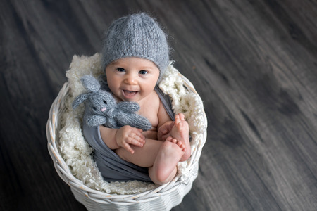Sweet baby boy in basket, holding and hugging teddy bear, looking curiously at camera, smiling Stock fotó