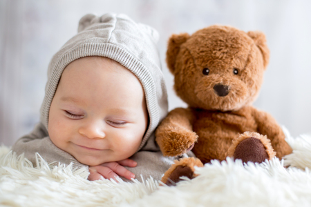 Sweet baby boy in bear overall, sleeping in bed with teddy bear stuffed toys, winter landscape behind him Stockfoto