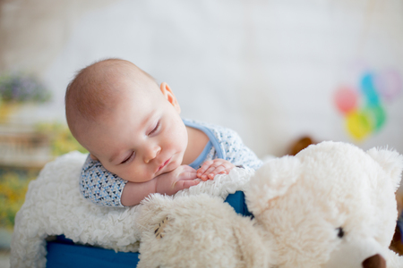 Little baby boy with knitted hat, sleeping with cute teddy bear toy at home