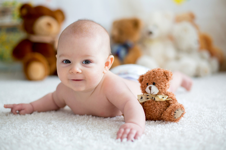 Little baby boy playing at home with soft teddy bear toys, lying down Banco de Imagens