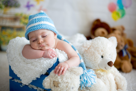 Little baby boy with knitted hat, sleeping with cute teddy bear toy at home Banco de Imagens - 92882387