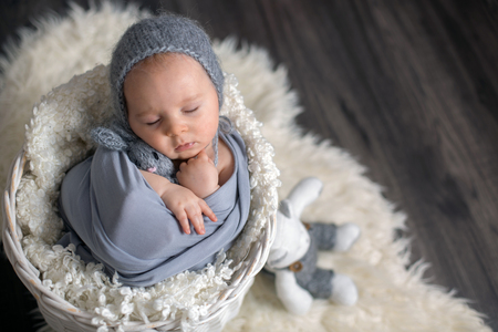 Sweet baby boy in basket, holding and hugging teddy bear, peacefully sleeping wrapped in grey scarf Stock fotó