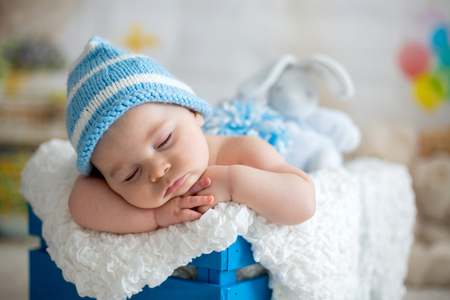 Little baby boy with knitted hat, sleeping with cute teddy bear toy at home Banco de Imagens - 93477796