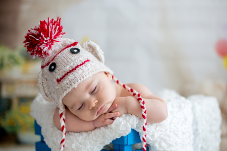 Little baby boy with knitted hat, sleeping with cute teddy bear toy at home Banco de Imagens - 93477798