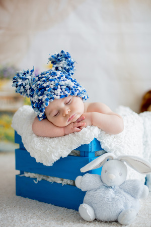 Little baby boy with knitted hat, sleeping with cute teddy bear toy at home Banco de Imagens - 93477801