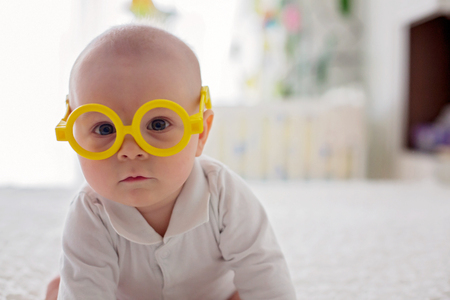 Little baby boy, toddler, playing at home with funny eye glasses in bed in bedroom Imagens