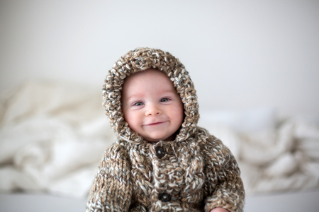 Little baby boy playing at home in bed, dressed in hand made knitted bear overall Banco de Imagens