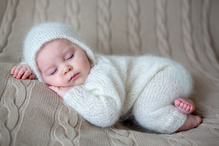 Beatiful baby boy in white knitted cloths and hat, sleeping sweetly posed in bed Banco de Imagens