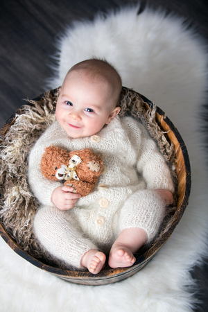Cute little baby boy with handmade knitted cloths, playing with little teddy bear toy, smiling at camera Фото со стока