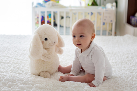 Little baby boy, toddler, playing at home with plush toy in bed in bedroom