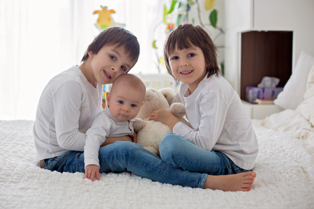 Little toddler and preschool boys, playing with their little brother at home in bedroom Stock Photo