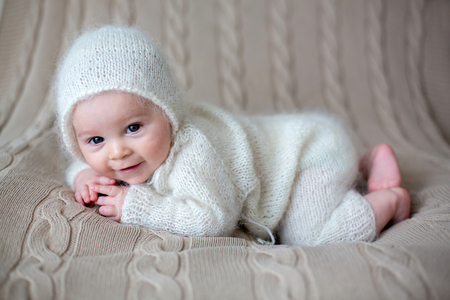 Beatiful baby boy in white knitted cloths and hat, looking curiously posed in bed
