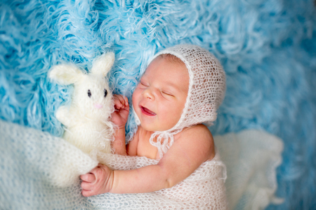Little cute newborn baby boy, sleeping wrapped in white wrap, holding little knitted toy