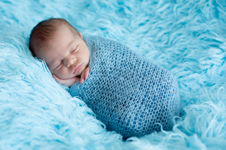 Cute baby boy, peacefully sleeping wrapped in blue wrap on a blue fur, in potato sack