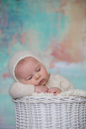 Little cute baby boy, dressed in handmade knitted white teddy bear overall, sleeping peaefully with little knitted toy in basket
