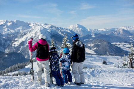 Happy family, mother, father and two children, skiing in Austrian Alps