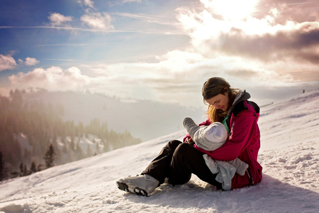 Young mother, breastfeeding her baby boy on top of mountain on sunset in Austrian Alps, beautiful scenery landscape