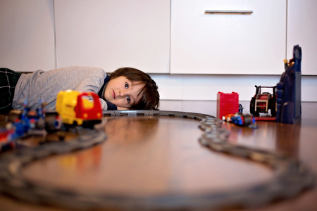 Child boy playing in living room on the floor with a toy train Stockfoto
