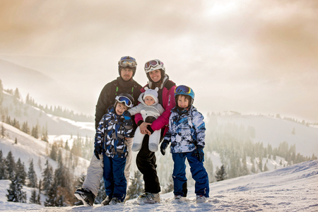 Beautiful family with kids, skiing in a scenery area in Austrian Alps on sunset, enjoying the view of the snowy mountains