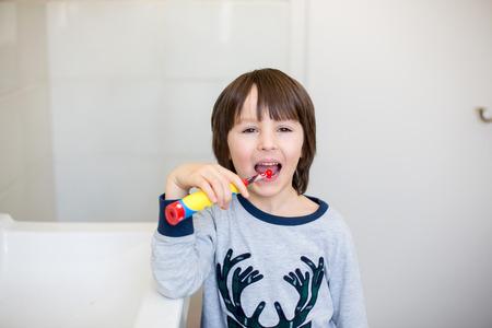 Preschool boys, brushing their teeth in bathroom, sunny day, kids in pajamas in the morning