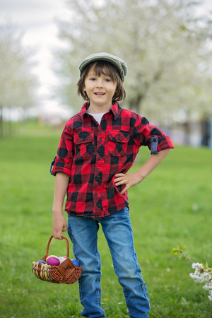 Two children, boy brothers, having fun with easter eggs in the park, beautiful spring blooming garden