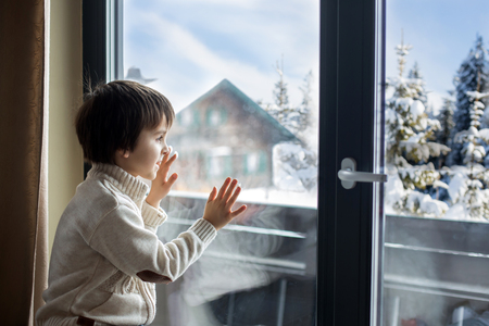 Preschool boy, sitting by the window in living room, looking at a snowy landscape outdoors, winter snowing weather