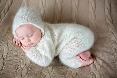 Beatiful baby boy in white knitted cloths and hat, sleeping sweetly posed in bed Stock Photo