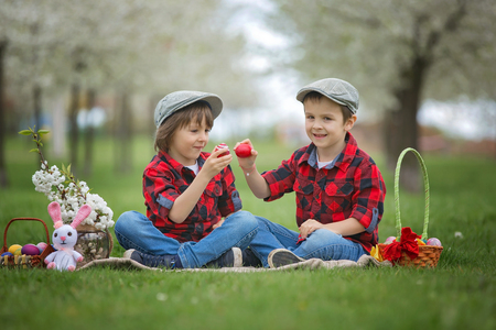 Two children, boy brothers, having fun with easter eggs in the park, beautiful spring blooming garden Stock Photo