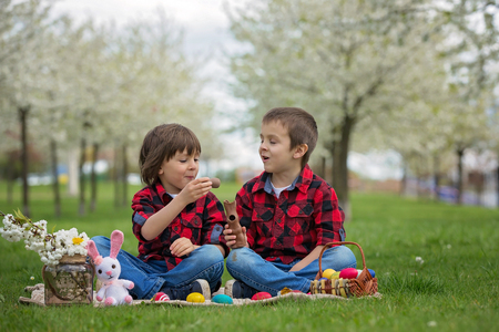 Two children, boy brothers, eating chocolate bunnies and having fun with easter eggs in the park, beautiful spring blooming garden