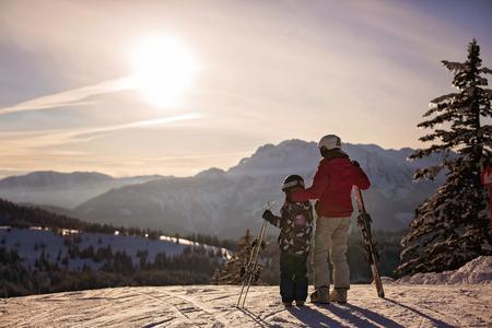 母と息子、就学前の子供、オーストリアアルプスの夕日に一緒にスキー、幸せな家族のコンセプト 写真素材