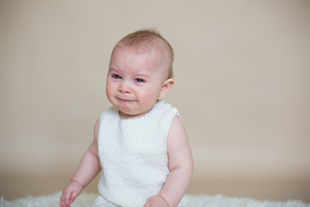 Close portrait of cute little baby boy, isolated on beige background, baby making different facial expressions, crying, sad, smiling, laughing