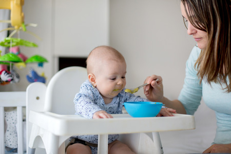 Cute little baby boy, eating mashed vegetables for lunch, mom feeding him, sweet toddler boy, smiling Imagens