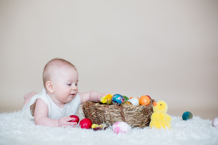 Cute little toddler baby boy, playing with colorful easter eggs and little decorative ducks, isolated shot, beige background