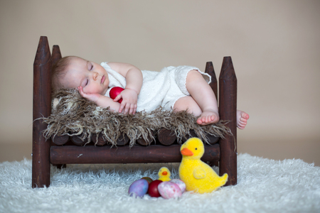 Cute little toddler baby boy, sleeping with colorful easter eggs and little decorative ducks, isolated shot, beige background