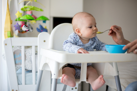 Cute little baby boy, eating mashed vegetables for lunch, mom feeding him, sweet toddler boy, smiling Фото со стока
