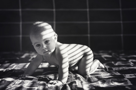 Cute portrait of little toddler boy in bed, sun ight falling on him on stripes through sun blinds in the afternoon
