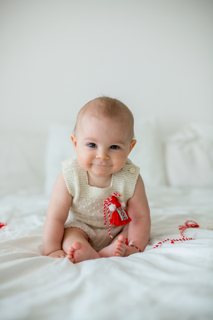 Cute baby toddler boy, playing with white and red bracelets.