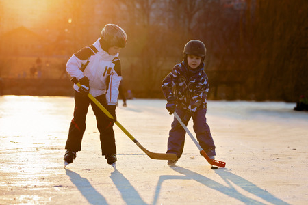 Children, boys, friends and brothers playing hockey and skating in the park on frozen lake, wintertime on sunset