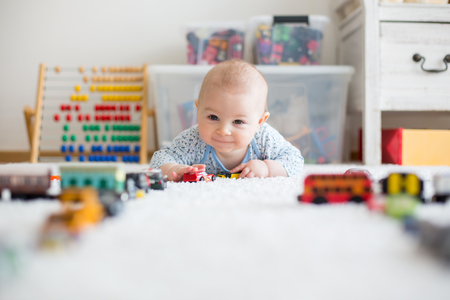 Cute little baby boy, playing with toy cars on the carpet in sunny kids room