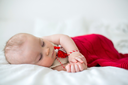 Cute baby toddler boy, sleeping with white and red bracelet. Stock Photo
