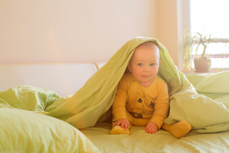 Cute baby boy, playing in bed morning time, smiling happily
