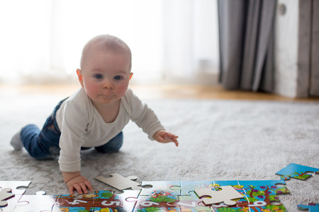 Cute little baby boy, playing at home, crawling and playing with toys