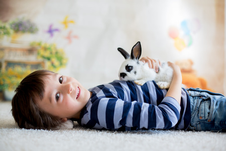 Cute little toddler boy, dressed smart casual, playing with little black and white rabbit at home