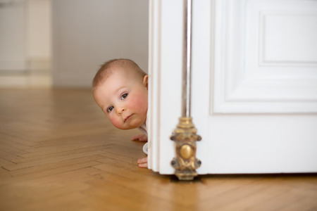 Little baby boy, toddler, in a long hall, crawling on the floor, smiling Фото со стока - 99247613