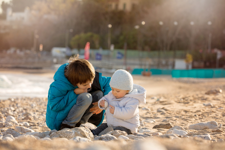 Cute boys, preschool child and toddler baby, playing on the beach on sunset with sand pebbles